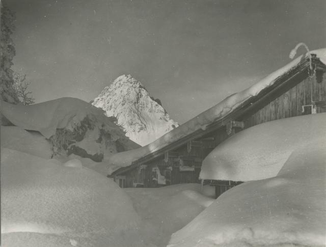 Deeply snow-covered gable end of wooden chalet with mountain peak in background by Erich Retzlaff (Aberystwyth University School of Art)