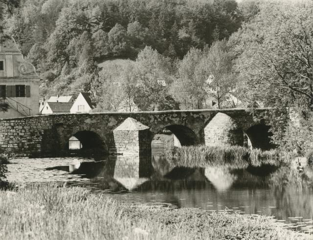 Stone bridge reflected in river with wooded background by Erich Retzlaff (Aberystwyth University School of Art)